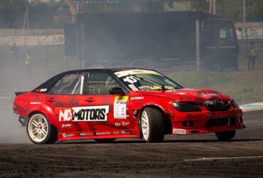 Красный гоночный автомобиль в дыму