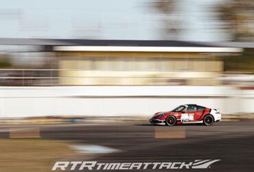 красный гоночный автомобиль на трасе тайматак