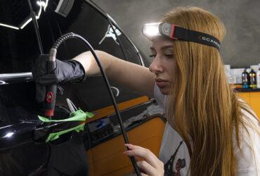 студентка полирует участки под дверными ручками авто